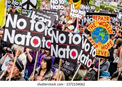 """LONDON, UK - 19 May 2012: people hold placards reading 'No to NATO' and 'Don't attack Iran"""" during an anti-war pacifist rally outside the US Embassy in London"""