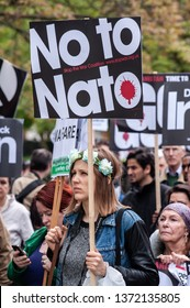 LONDON, UK - 19 May 2012: a young woman holds a placard reading 'No to NATO' during an anti-war pacifist rally outside the US Embassy in London