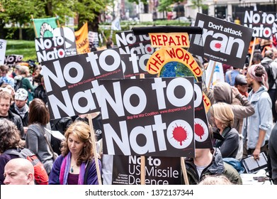 """LONDON, UK - 19 May 2012: peaople hold placards reading 'No to NATO' and ' Don't attack Iran"""" during an anti-war pacifist rally outside the US Embassy in London"""