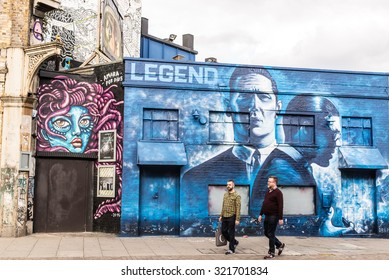 London, UK - 19 September 2015: Two middle aged men walking in front of street graffiti promoting the release of the movie Kray's Legend. Shot in Shoreditch an area of London famous for street art.