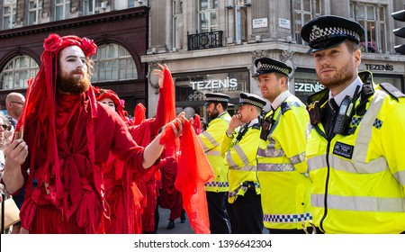 London, UK, 19th April 2019. Performance troupe Red Brigade parade at the Extinction Rebellion demonstration, at Oxford Circus, London, in protest of world climate breakdown and ecological collapse.