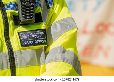 London, UK. 19th April 2019. Close up of badge & mobile phone being worn by a Metropolitan Police Officer, to connect with HQ, at the Extinction Rebellion protest demonstration in central London, UK.