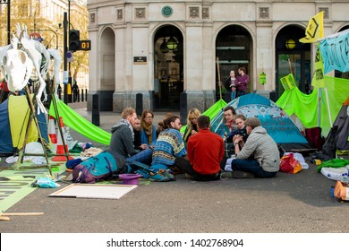 London, UK. 19th April 2019. Extinction Rebellion supporters occupy & block the road in Parliament Square, central London, with tents, in protest against world climate change and ecological collapse.