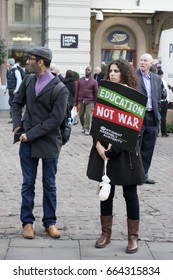 "London, UK. 19th Nov, 2016. Students protest against fees and cuts and debt in central London. A girl with curly hair is holding a poster ""Education, no war"""