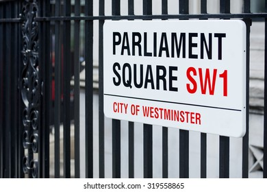 London, UK. 19th September 2015. The London street sign for Parliament Square, SW1. The sign is attached to black metal railings, and viewed from an angle.