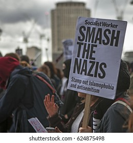 """London, UK. 1st April, 2017. A supporter of Unite Against Fascism protests against a march by far-right group the English Defence League. Poster with inscription """"Smash the Nazis"""""""