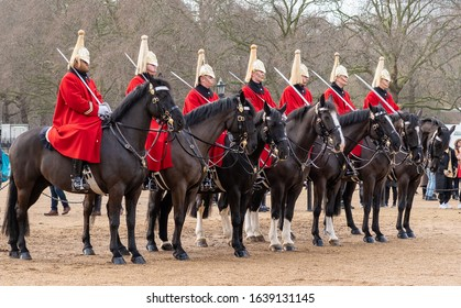 London / UK - 2 Feb 2020: Seven Life Guards of the Household Cavalry wear dress uniforms of red wool greatcoats (frock) and gold helmets. Regimental horses wait patiently at Horse Guards Parade.