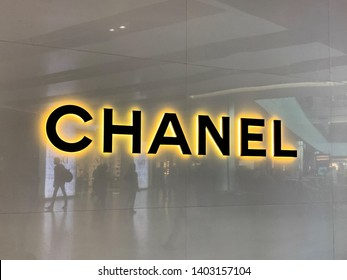 London, UK - 20th May 2019: Chanel store in Heathrow airport shopping mall. Duty Free shop with passengers reflected in the facade. Iconic sign of this French Design House.