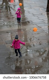 London, UK, 21 January 2018: A girl enjoying splashing in puddles on a rainy day on London's South Bank