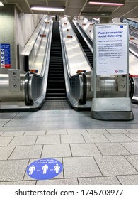 London, UK - 22 May 2020: Empty escalator at Kings Cross Tube station with sign encouraging Social Distancing. The usually busy station is almost empty as people are staying at home for the lockdown