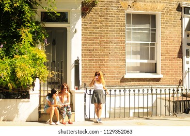 London, UK - 23 June 2018 : Woman are sitting in front of the house at the portobello market on holiday at weekend on background nature view