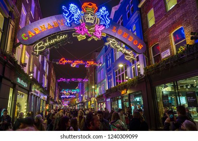 London,  UK - 23 November, 2018: Crowds of Black Friday holiday shoppers walk past the shops of Carnaby Street under colorful Bohemian Rhapsody musical themed Christmas lights.