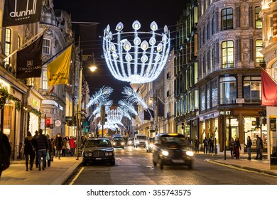 LONDON, UK - 23RD DECEMBER 2015: A view down New Bond Street in London during the Christmas period showing building exteriors, decorations, people and traffic.