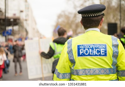 London, UK. 23rd March 2019. Metropolitan Police sign on the back of a high visibility jacket worn by police officers escorting & monitoring a street demonstration through central London, UK.