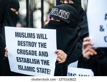 "London, UK - 24 January 2014: a woman holds a placard reading ""Muslims will destroy the crusade and estabilish the Islamic State!"" outside the Regents Park Mosque."