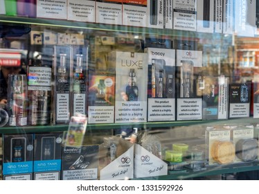LONDON, UK - 26 FEBRUARY, 2019: Many brands of e-cigarettes in shop with reflection of street in window