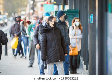 London, UK - 26 February, 2021 - Customers with face masks queueing outside the shop during the COVID-19 pandemic