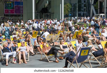 London, UK - 26 June, 2018: City of London business and banking aria at lunch time. Lots of people chilling out on the sun.
