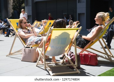 LONDON, UK - 26 June, 2018: Three young woman relaxing in the City of London at lunch time. Square next to the Lloyds building