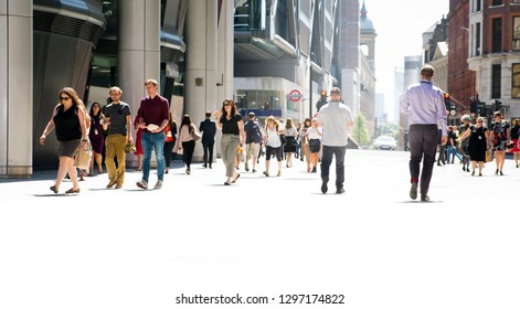 LONDON, UK - 26 June, 2018: Group of people walking in the City against of sun light in hot summer day. Beautifully lit up street by the sun, City of London modern busy concept. Wide panoramic view