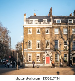 LONDON, UK - 27 FEBRUARY 2019: The facade to a typical London Georgian town house in Bedford Square bathing in the dusk sunlight with passing pedestrians.