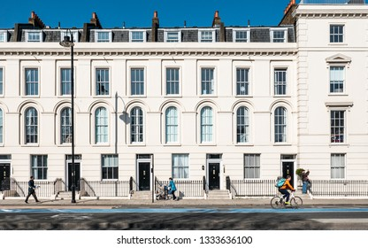 LONDON, UK - 27 FEBRUARY 2019: Human traffic passing the bright uniform facade of a row of typical Georgian town houses found in central London.
