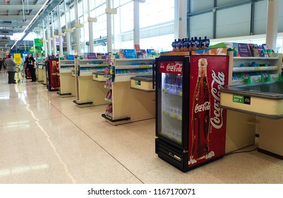 London, UK - 28 August 2018: Coke cooler fridge at the end of a long aisle of checkout till register counters in a supermarket.