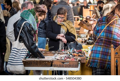 LONDON, UK - 28 JANUARY 2016: Spitalfield's antique market. Shoppers looking through items for sale at London's popular Spitalfields market.