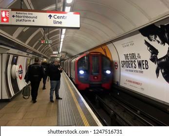 LONDON, UK - 28 NOV 2018: Man checks his phone as tube train arrives at platform on London Underground