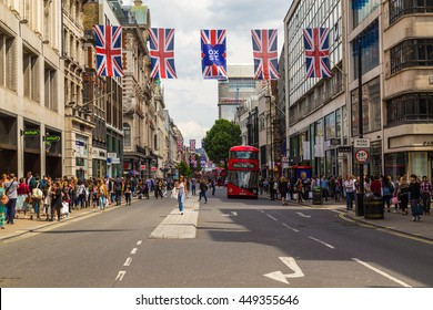 LONDON, UK - 28TH JUNE 2016: A view along Oxford Street in London during the day. London Red double decker Buses,  union jack flags and lots of people can be seen.