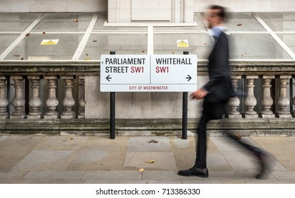LONDON, UK - 29 AUGUST 2017: Whitehall civil servant. Anonymous blur of a suited office worker passing a street sign for Parliament Street and Whitehall in the civil service district of Westminster.