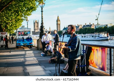 London, UK - 29 June 2016: Street musician near the Big Ben with Thames River.
