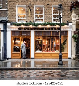 LONDON, UK - 3 DECEMBER 2018: A smartly dressed sales shopper standing in the doorway of the exlusive Mariage Freres tea company in Covent Garden, London.