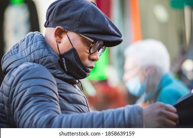 London, UK - 3 November, 2020 - A black man wearing a face mask improperly while shopping at Walthamstow market, wrong way, incorrect wearing