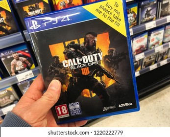 London, UK - 30 October 2018: A shopper customers hand holding a call of duty black ops 4 playstation xbox one action shooter video game on display in a store supermarket shop.