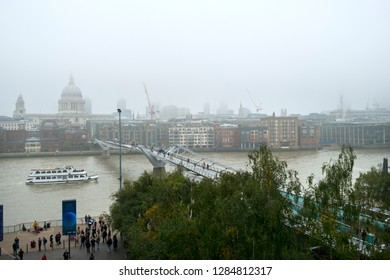 London, UK - 30th October 2016: Looking across the River Thames and the London Millennium Footbridge towards St Pauls Cathedral and The City of London on a foggy autumn day