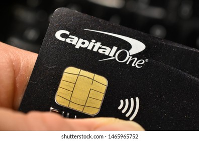 London, UK - 31 July 2019: A hand holding a capital one credit debit loan finance wireless contactless bank card and chip.