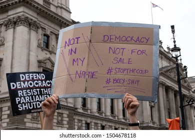 """London, UK - 31/08/19: Protest against the shutdown of parliament and Brexit. """"Not in my name Democracy not for sale #stopthecoup #brex-shit"""" and """"Defend Democracy Resist The Parliament Shutdown"""" sign"""