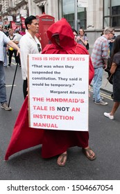 """London, UK - 31/08/2019: """"Stop the Coup"""" demonstration against the suspension of parliament and Brexit. Woman dressed up as a handmaid from Margaret Atwoods Handmaids Tale."""