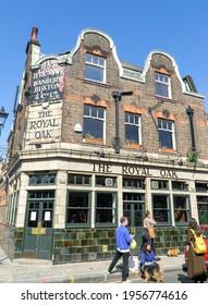 London, UK: 4 April 2021:People walking outside the Royal Oak pub, Columbia Road, Bethnal Green, East London