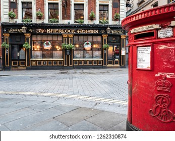 LONDON, UK - 4 DECEMBER 2018: An old red post box outside a traditional English pub, The Sherlock Holmes, in Westminster. Please note, Christmas decorations in the pub windows.