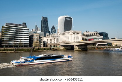 LONDON, UK - 6 APRIL 2017: London River Bus. A view of an MBNA Thames Clipper river bus on the River Thames with London Bridge and the financial skyscrapers of the City of London in the background.
