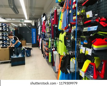 London, UK - 6 September 2018: Woman putting out clothes in a shop aisle with shelves full of sporting goods in a Decathlon shopping center mall.