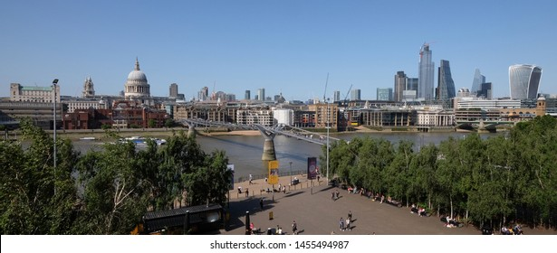 London, UK 6th July 2019: London skyline panorama seen from south bank, St Pauls Cathedral and river Thames in foreground on summer day, tourists on the millennium bridge