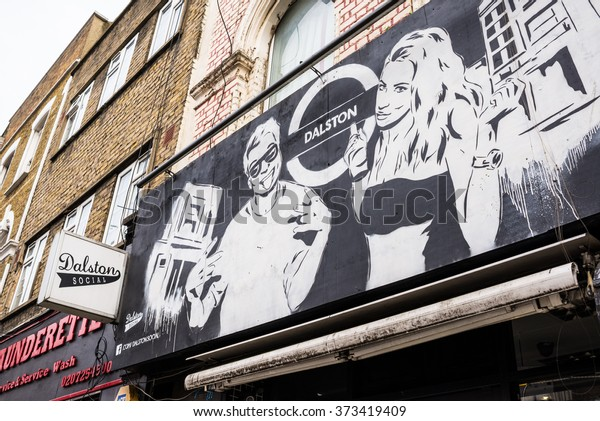 London, UK - 7 February 2016: Graffiti sprayed mural representing a cool hipster couple in front of Dalston Social, a popular venue  in the heart of Dalston's busy Stoke Newington Road in East London.