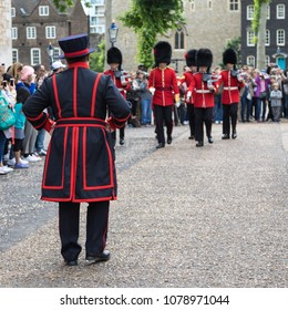 London, UK - 7th June 2017: Rear view of a Beefeater and the Queens Guard on parade at the Tower of London, in traditional red and black uniform with bearskin hats.