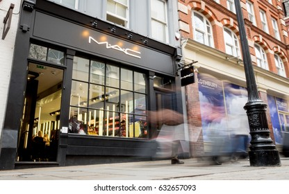 LONDON, UK - 8 MARCH 2017: Long exposure, blurred shoppers walking by the high street cosmetic and make-up brand, Mac, on a pedestrianised street near Covent Garden, London.