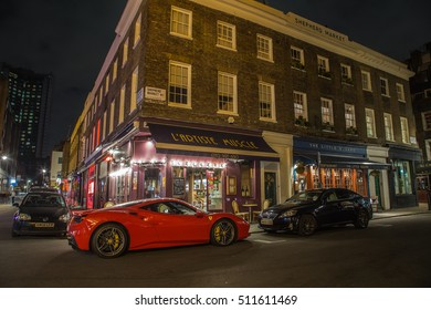 LONDON, UK - 8TH OCTOBER 2016: The outside of buildings near Shepherd Market in Mayfair London at night. Buildings and people can be seen.