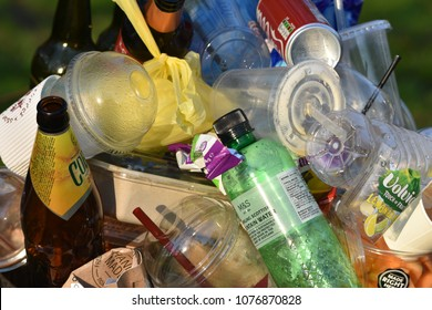 London UK Apr 18 2018. Piled up garbage of single use waste food/drink containers including single use plastic waste, bottles, straws at the top of an overflowing general garbage bin in a public park
