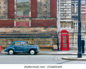 London / UK - April 05 2008: An old blue car is parked in front of Victoria & Albert Museum and next to traditional English red phone booth
